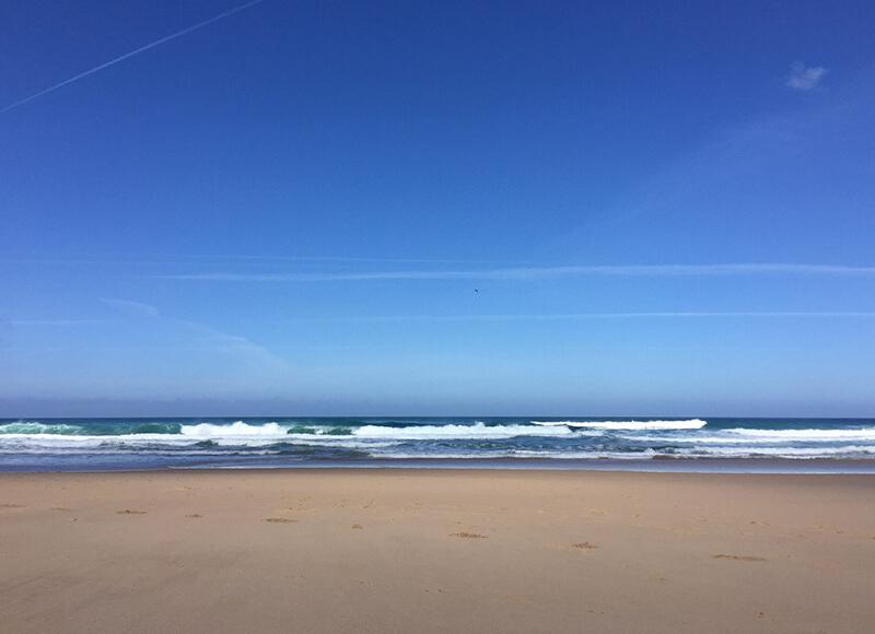 An einen weiten Strand rollen sanft die Wellen.