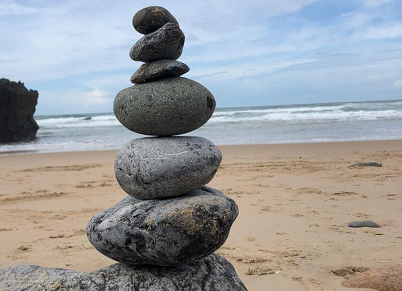 Kleine Steinpyramide am Strand vor den Wellen.